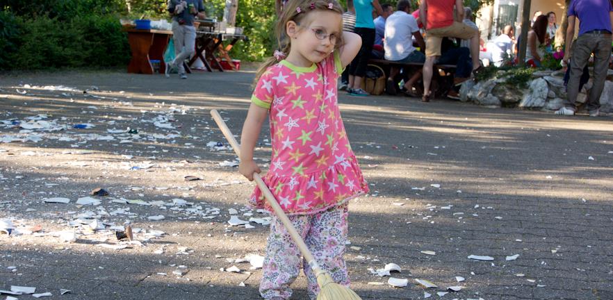 Kleines Mädchen mit Besen beim kehren der Scherben am Polterabend